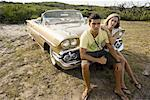 Young couple sitting on front bumper of antique convertible car