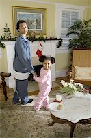 View of brother and sister standing by fireplace decorated for Christmas, waiting for Santa Stock Photo - Premium Royalty-Freenull, Code: 638-01333363