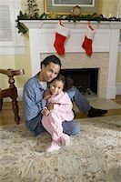 View of brother and sister sitting by fireplace decorated for Christmas, waiting for Santa Stock Photo - Premium Royalty-Freenull, Code: 638-01334397