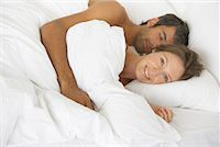 Woman and man lying down in bed Stock Photo - Premium Royalty-Freenull, Code: 635-01346608