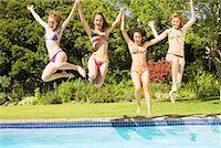 Four teenage girls jumping into pool Stock Photo - Premium Royalty-Freenull, Code: 635-01347022