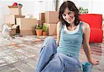 Woman sitting on hardwood floor with mug and cardboard boxes smiling Stock Photo - Premium Royalty-Free, Artist: Arcaid, Code: 635-01347064