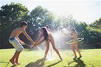 Teenage boy spraying teenage girls with hose outdoors Stock Photo - Premium Royalty-Freenull, Code: 635-01347313