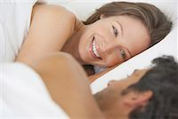 Woman and man lying down in bed Stock Photo - Premium Royalty-Freenull, Code: 635-01347395
