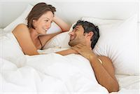Woman and man lying down in bed Stock Photo - Premium Royalty-Freenull, Code: 635-01347485