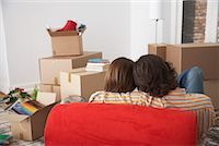 red chair - Rear view of couple on red chair in house with cardboard boxes Stock Photo - Premium Royalty-Freenull, Code: 635-01347841