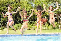 Four teenage girls jumping into pool Stock Photo - Premium Royalty-Freenull, Code: 635-01347879