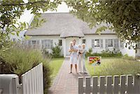 sold sign - Man and woman holding babies in front of house with sold sign and white fence Stock Photo - Premium Royalty-Freenull, Code: 635-01348155