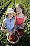 Portrait of two girls with baskets of strawberries on a field Stock Photo - Premium Royalty-Free, Artist: Flowerphotos, Code: 640-01348598