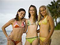 Portrait of three teenage girls standing on the beach and smiling Stock Photo - Premium Royalty-Freenull, Code: 640-01349686