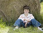 Portrait of a boy sitting against a hay bale Stock Photo - Premium Royalty-Free, Artist: Eyecandy Pro, Code: 640-01349729