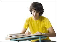 Close-up of a teenage boy writing in a notebook Stock Photo - Premium Royalty-Freenull, Code: 640-01350635