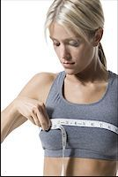 A young woman measuring her chest with a measuring tape Stock Photo - Premium Royalty-Freenull, Code: 640-01351372