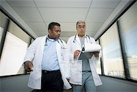Low angle view of two male doctors walking in a hospital corridor Stock Photo - Premium Royalty-Freenull, Code: 640-01351505