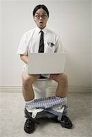Portrait of a young man sitting on a toilet using a laptop Stock Photo - Premium Royalty-Freenull, Code: 640-01352245