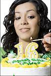 Close-up of a teenage girl looking at a person lighting candles on her birthday cake Stock Photo - Premium Royalty-Free, Artist: AlaskaStock              , Code: 640-01352456
