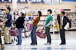 People waiting in line with shopping baskets at grocery store Stock Photo - Premium Royalty-Free, Artist: Noel Hendrickson, Code: 640-01352749