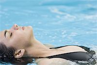 High angle view of a young woman floating in a swimming pool Stock Photo - Premium Royalty-Freenull, Code: 640-01352982