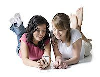 Close-up of two girls listening to music on an MP3 player Stock Photo - Premium Royalty-Freenull, Code: 640-01353317