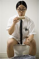 Close-up of a young man sitting on a toilet Stock Photo - Premium Royalty-Freenull, Code: 640-01353427