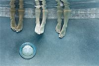 Low section view of three teenage girls feet in a swimming pool Stock Photo - Premium Royalty-Freenull, Code: 640-01353487