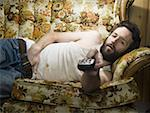 Man on sofa with television remote Stock Photo - Premium Royalty-Free, Artist: Jerzyworks, Code: 640-01354186