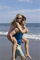 Young man carrying a young woman on his back Stock Photo - Premium Royalty-Freenull, Code: 640-01354640