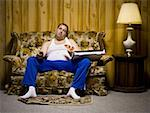 Man on sofa with pizza and TV remote Stock Photo - Premium Royalty-Free, Artist: Masterfile, Code: 640-01354948