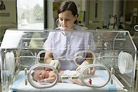 Female nurse examining a newborn baby in an incubator Stock Photo - Premium Royalty-Freenull, Code: 640-01355635