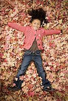pile leaves playing - Young girl playing in fallen leaves Stock Photo - Premium Royalty-Freenull, Code: 640-01355877