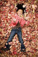 pile leaves playing - Young girl playing in fallen leaves Stock Photo - Premium Royalty-Freenull, Code: 640-01356746