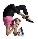 Female contortionist talking on phone and ironing