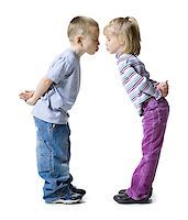 people kissing little boys - Profile of a boy and a girl almost kissing each other with their hands behind their backs Stock Photo - Premium Royalty-Freenull, Code: 640-01357420