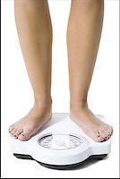 Dieting woman standing on bathroom scale Stock Photo - Premium Royalty-Freenull, Code: 640-01357765