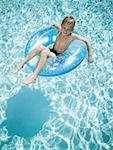 Young boy floating on life ring in swimming pool Stock Photo - Premium Royalty-Free, Artist: George Shelley, Code: 640-01357881