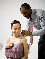 Man putting on a necklace around a woman's neck Stock Photo - Premium Royalty-Freenull, Code: 640-01358184