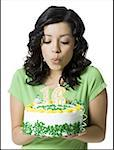 Close-up of a teenage girl blowing out candles on her birthday cake Stock Photo - Premium Royalty-Free, Artist: Aurora Photos, Code: 640-01359844