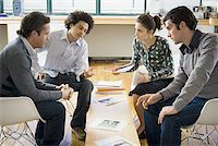 Four people discussing ad layouts Stock Photo - Premium Royalty-Freenull, Code: 640-01360790