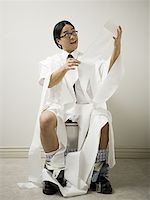 Close-up of a young man sitting on a toilet Stock Photo - Premium Royalty-Freenull, Code: 640-01361177