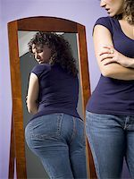 Young woman looking at her buttocks in the mirror Stock Photo - Premium Royalty-Freenull, Code: 640-01362029