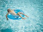 Young boy floating on life ring in swimming pool Stock Photo - Premium Royalty-Free, Artist: Tim Mantoani, Code: 640-01362130