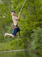 Portrait of a boy swinging on a rope Stock Photo - Premium Royalty-Freenull, Code: 640-01362943