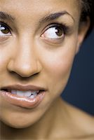 Woman looking up biting lip Stock Photo - Premium Royalty-Freenull, Code: 640-01363041