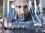Close-up of businessman watching a Newton's cradle Stock Photo - Premium Royalty-Free, Artist: Gary Rhijnsburger, Code: 640-01363623