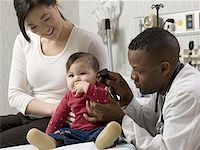 Profile of a male doctor examining a baby Stock Photo - Premium Royalty-Freenull, Code: 640-01365523