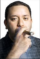 Portrait of a mid adult man smoking a cigar Stock Photo - Premium Royalty-Freenull, Code: 640-01365574