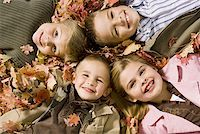 pile leaves playing - Young kids playing in a pile of fallen leaves Stock Photo - Premium Royalty-Freenull, Code: 640-01366112