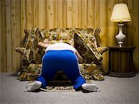 Man looking under sofa cushion Stock Photo - Premium Royalty-Freenull, Code: 640-01366268