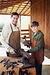 Man and teenage boy working on horseshoes Stock Photo - Premium Royalty-Free, Artist: AWL Images, Code: 621-01375183