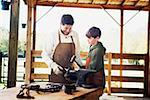 Father watching son shaping horseshoe with mallet Stock Photo - Premium Royalty-Free, Artist: ableimages, Code: 621-01375185